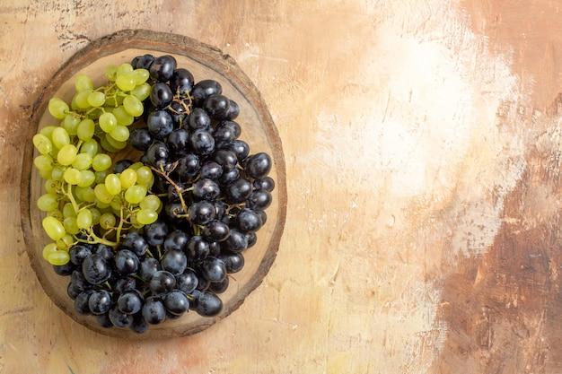 Vista dall'alto grappoli di uva verde e nera sul tagliere di legno