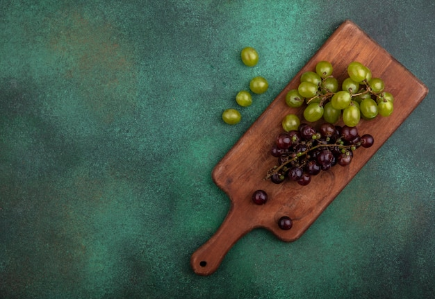 Top view of grapes on cutting board with grape berries on green background with copy space