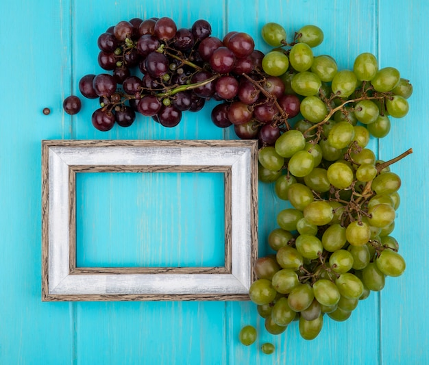 Top view of grapes and frame on blue background with copy space
