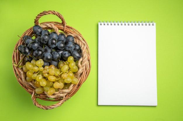 Vista dall'alto taccuino bianco dell'uva grappoli d'uva sul tavolo verde