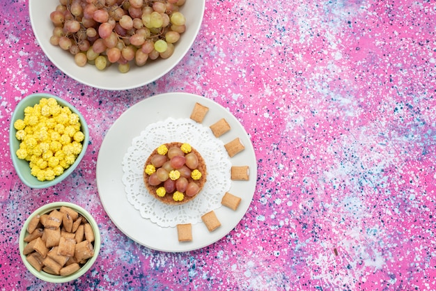 Top view grapes with candies on the colorful background cookie crisp cracker fruit color