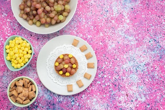 Вид сверху виноград с конфетами на красочном фоне, печенье, хрустящий крекер, цвет фруктов