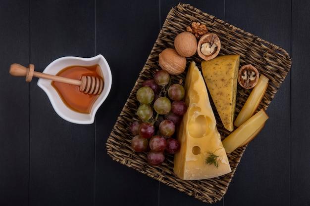 Vista dall'alto uva con vari formaggi e noci su un supporto con miele in un piattino su uno sfondo nero
