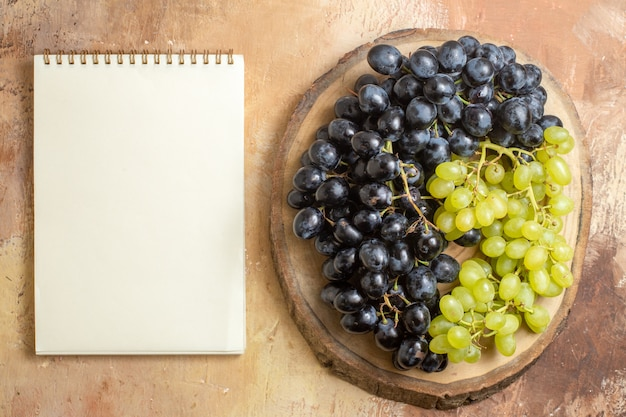 Top view grapes wooden board with green and black grapes next to the white notebook