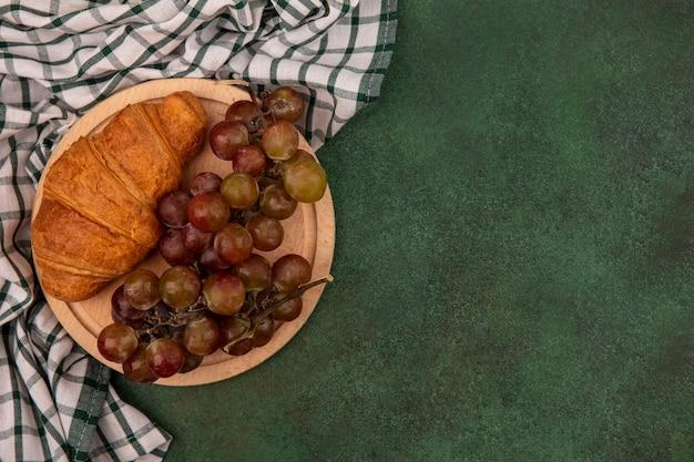 Vista dall'alto di uva su una tavola da cucina in legno con croissant su un panno controllato su una superficie verde con spazio di copia