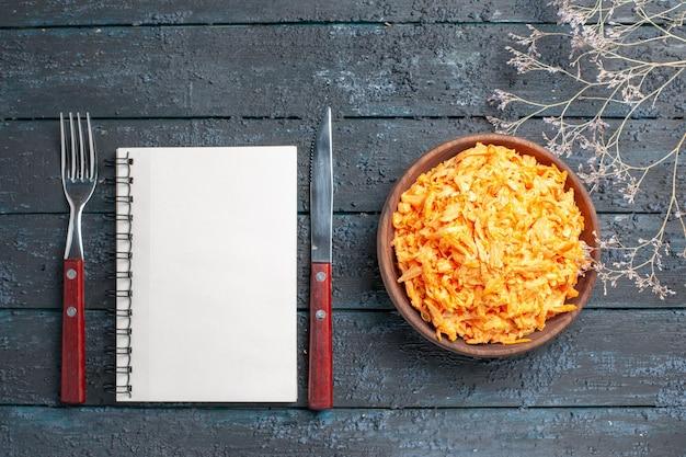 ダークブルーの素朴な机の上の茶色のプレート内の上面のすりおろしたにんじんサラダ健康サラダ熟した野菜の食事療法の色