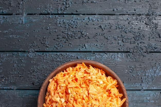 ダークブルーの素朴なデスクサラダの色熟した健康ダイエット野菜のプレート内のすりおろしたにんじんサラダの上面図
