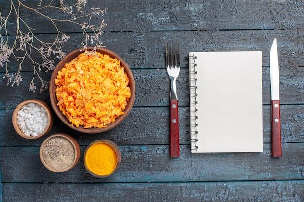 ダークブルーの素朴なデスクにニンニクと調味料を添えたトップビューのすりおろしたにんじんサラダ健康色サラダ熟した野菜ダイエット