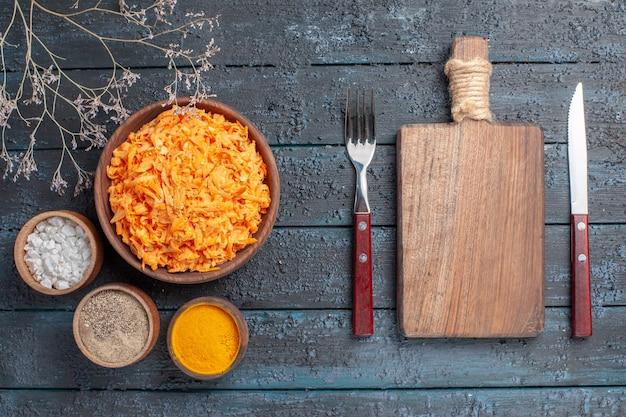 ダークブルーの素朴なデスクにニンニクと調味料を添えたトップビューすりおろしたにんじんサラダ健康色サラダ熟した野菜ダイエット