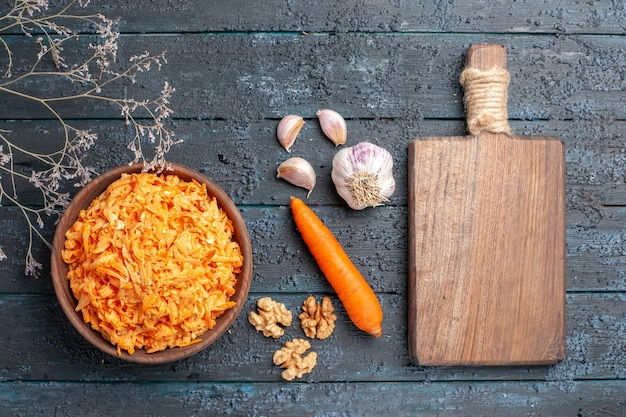 Top view grated carrot salad with garlic inside plate on dark-blue rustic desk health salad ripe vegetable color diet