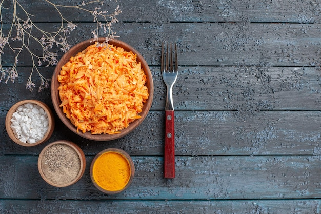 Top view grated carrot salad with garlic and seasonings on a dark-blue rustic desk health color salad ripe vegetable diet