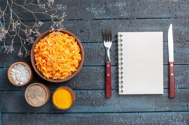 Top view grated carrot salad with garlic and seasonings on dark blue rustic desk health color salad ripe vegetable diet