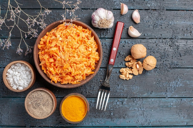 Top view grated carrot salad with garlic and seasonings on dark-blue rustic desk health color salad vegetable diet ripe