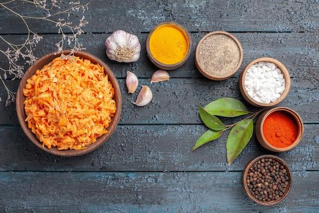 Insalata di carote grattugiate vista dall'alto con aglio e condimenti sulla dieta di verdure dell'insalata di colore della salute della scrivania rustica blu scuro matura