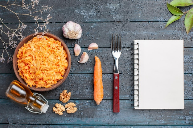 Top view grated carrot salad with garlic and walnuts on the dark-blue rustic desk health salad vegetables color diet ripe