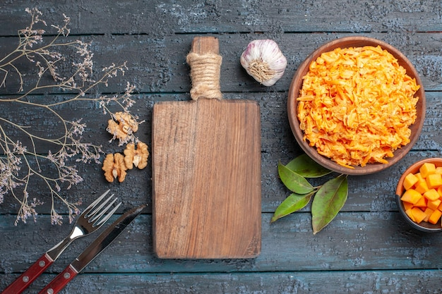 Top view grated carrot salad with garlic and walnuts on a dark rustic desk health diet salad ripe orange color