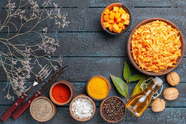 Top view grated carrot salad with garlic walnuts and seasonings on dark blue rustic desk health vegetable diet ripe salad color