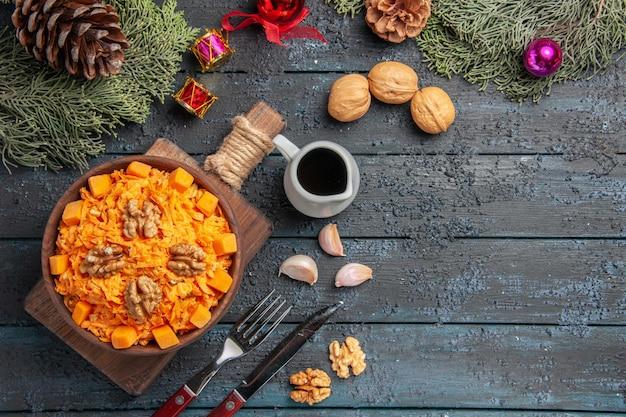 Вид сверху салат из тертой моркови с грецкими орехами и чесноком на темно-синем столе здоровое питание салат диетический цвет орехов