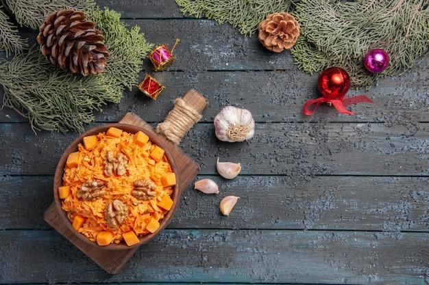 Vista dall'alto insalata di carote grattugiate con noci su sfondo blu scuro insalata di alimenti salutari color dieta dado