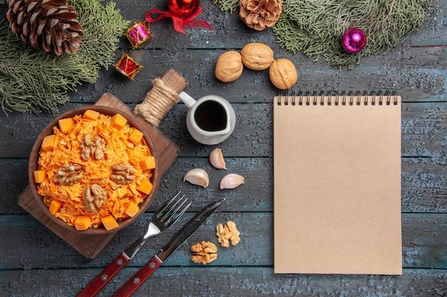 Vista dall'alto insalata di carote grattugiate con noci su scrivania blu scuro insalata di salute dieta noci cibo a colori