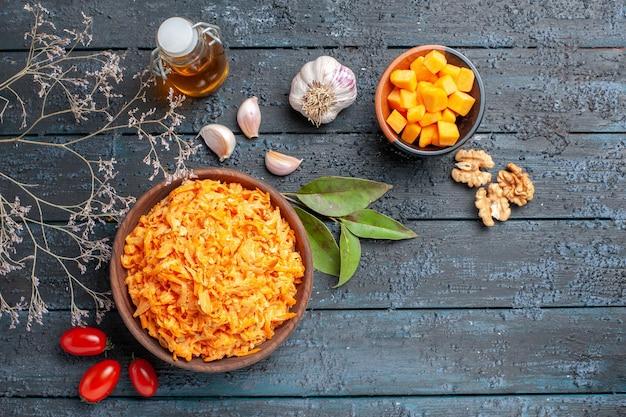 Vista dall'alto insalata di carote grattugiate con noci e aglio sullo sfondo scuro dieta salutare insalata matura di colore arancione