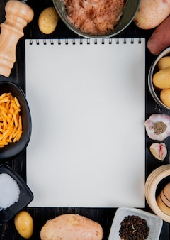 Top view of grated sliced and whole potatoes around note pad with salt black pepper on wooden surface with copy space