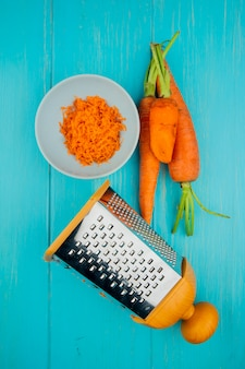 Top view of grated whole and cut carrot with metal grater on blue background