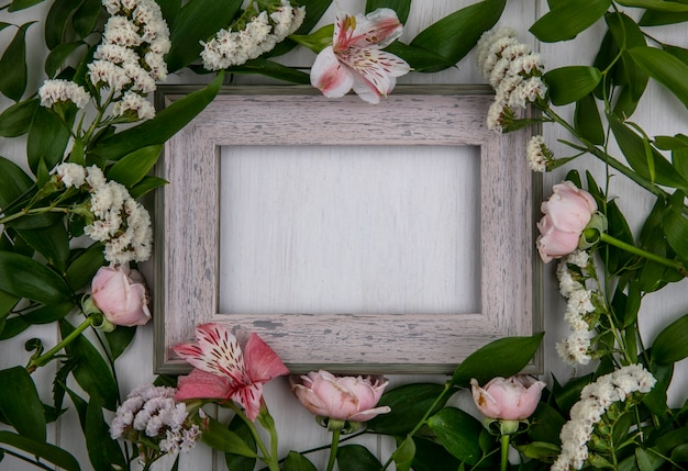 Top view of gray frame with leaf branches and light pink flowers on a gray surface