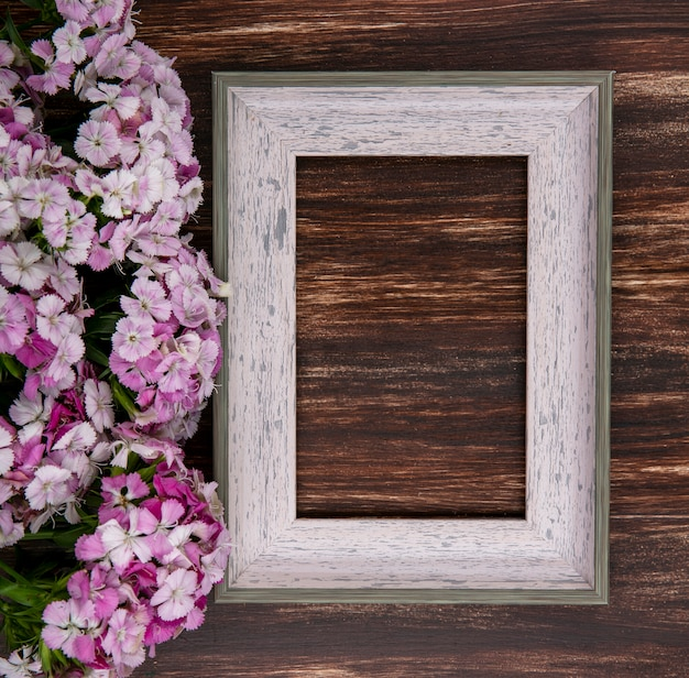 Top view of gray frame with light pink flowers on a wooden surface