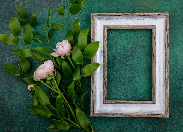 Top view of gray frame with light pink roses and leaf branches on a green surface