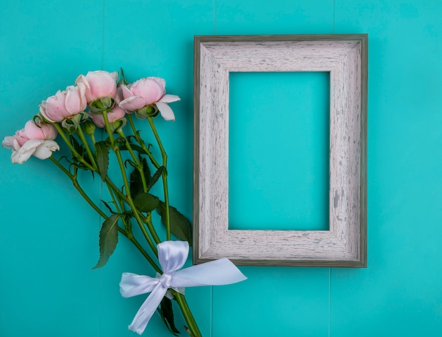 Top view of gray frame with light pink roses on a light blue surface