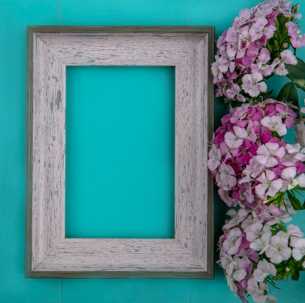 Top view of gray frame with light purple flowers on a light blue surface