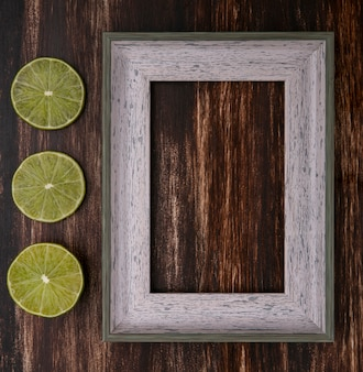 Top view of gray frame with lime slices on a wooden surface