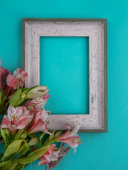 Top view of gray frame with pink lilies on a blue surface