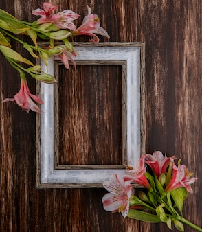 Top view of gray frame with pink lilies on a wooden surface