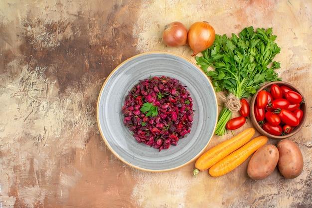 Vista dall'alto un piatto grigio con insalata di barbabietola sana e ingredienti per la sua preparazione su uno sfondo di legno con spazio per le copie