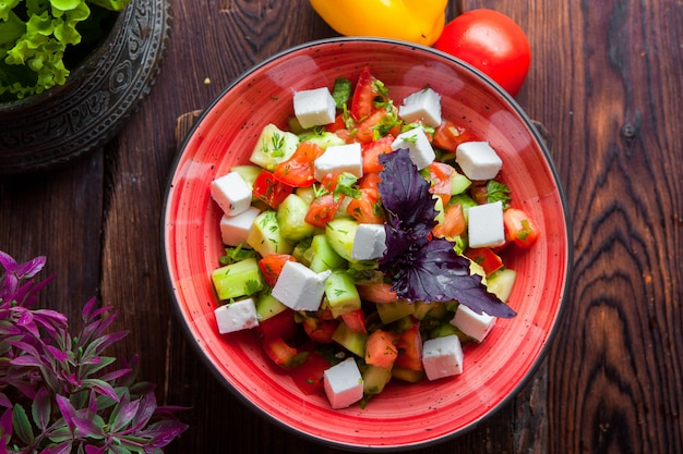 Top view greek salad lettuce, tomatoes, feta cheese, cucumbers, black olives, purple onion