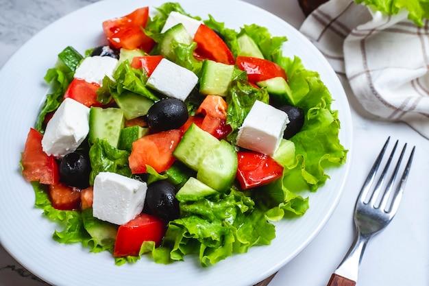 Вид сверху греческий салат на листьях салата с маслинами
