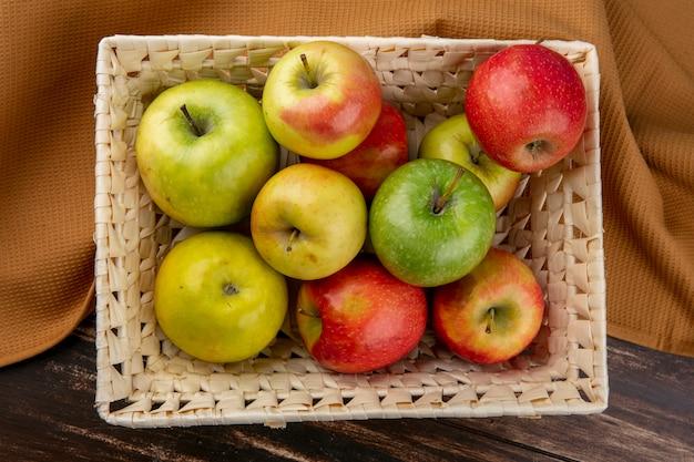 Вид сверху зеленые и красные яблоки в корзине на коричневом полотенце на деревянном фоне