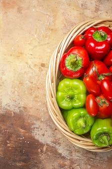 琥珀色の背景の枝編み細工品バスケットの上面図緑と赤のピーマントマト