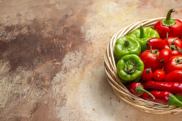 琥珀色の背景に籐のバスケットの上面図緑と赤唐辛子唐辛子トマト