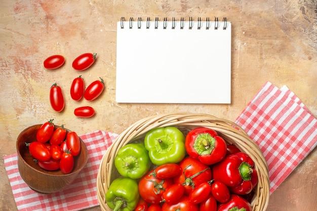 호박색 배경의 고리버들 바구니에 있는 상위 뷰 녹색 및 빨강 고추 토마토