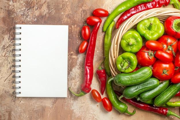トップビュー琥珀色の背景に籐のバスケット野菜ノートブックの緑と赤ピーマンのトマト