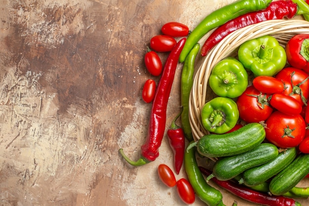 琥珀色の背景に籐のバスケット野菜の上面図緑と赤ピーマンのトマト