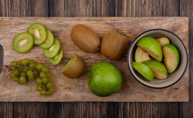 Vista dall'alto fette di mela verde in una ciotola con fette di kiwi e uva verde su una tavola su uno sfondo di legno