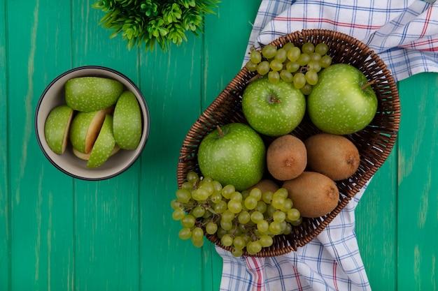 緑の背景にキウイとバスケットのブドウとボウルに青リンゴのくさびの上面図