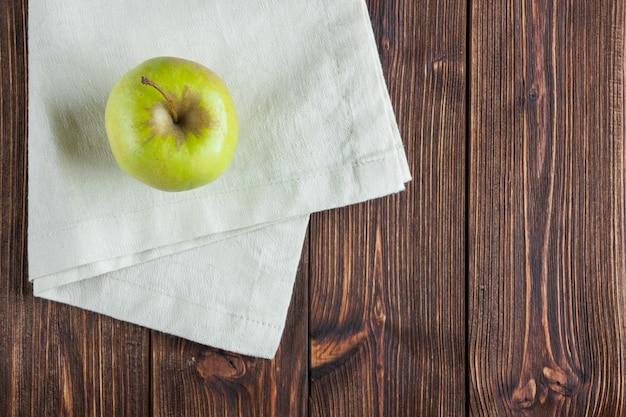 Mela verde di vista superiore sul panno bianco e sul fondo di legno. orizzontale, spazio per il testo
