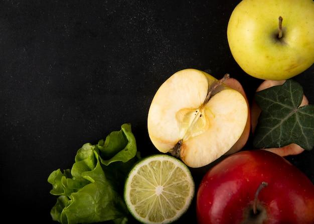 Вид сверху зеленое яблоко с ломтиком лимона, салатом красного яблока и копией пространства на черном фоне