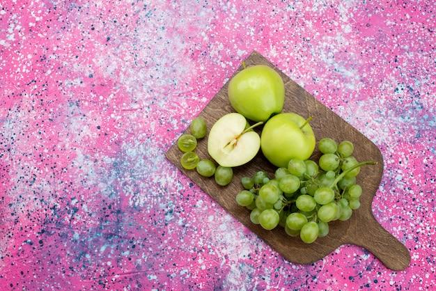 Вид сверху зеленые яблоки и зеленый виноград на фиолетовом столе фрукты спелые спелые цветные фото
