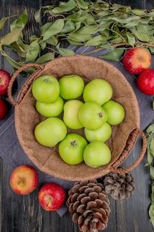 Vista superiore della merce nel carrello verde delle mele con i pinecones e le foglie rossi delle mele sul panno e sulla tavola di legno